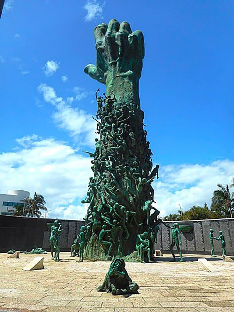 Statue d'une main qui sort de la terre et qui se tend vers le ciel au mémorial de l'Holocauste à Miami Beach